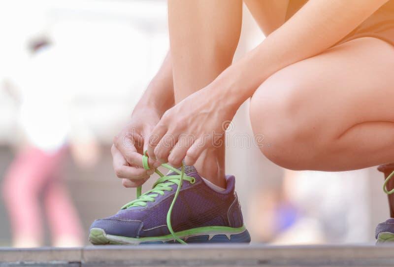 Kobieta wiąże działających buty dostaje przygotowywający dla jogging zdjęcia stock