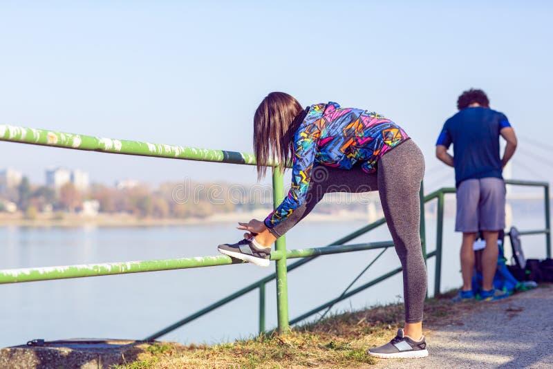 Kobieta wiąże jogging buty Biegać outdoors na słonecznym dniu zdjęcia royalty free