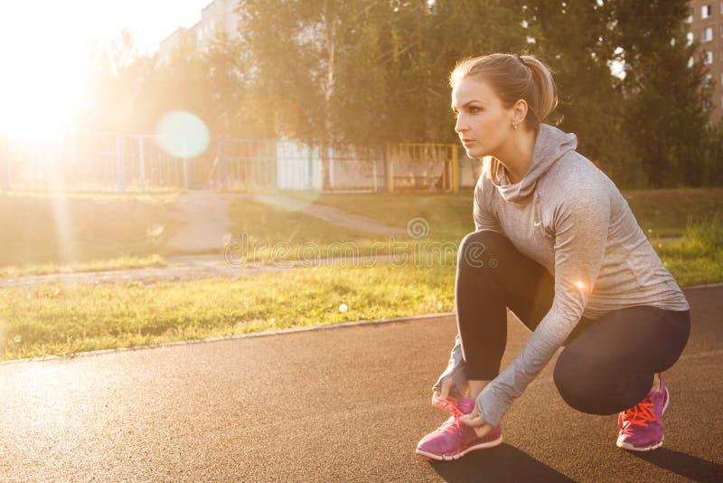 Kobieta wiąże obuwiane koronki Biegacz w lato parku zdjęcie royalty free