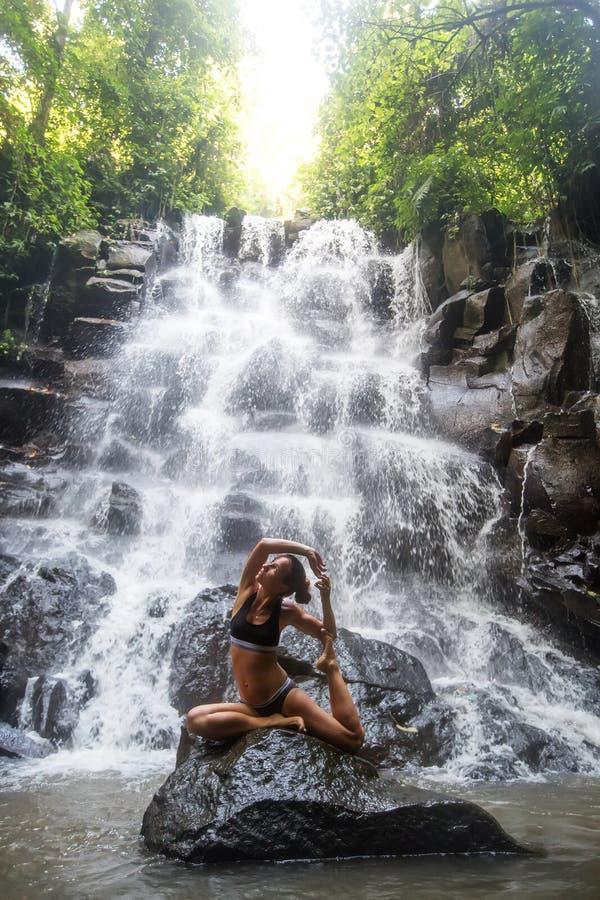 Kobieta ?wiczy joga blisko siklawy w Bali, Indonezja zdjęcia royalty free