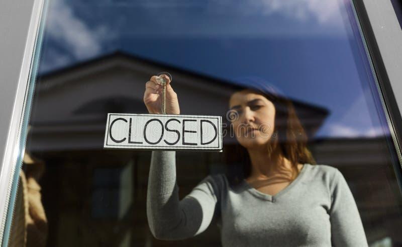 Kobieta wisząca baner z zamkniętym słowem na drzwiach zdjęcie royalty free