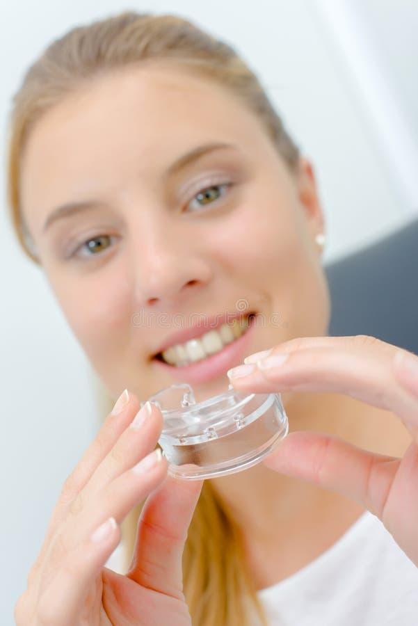 Kobieta wokoło używać usta strażnika podczas gdy przy dentystą zdjęcie stock
