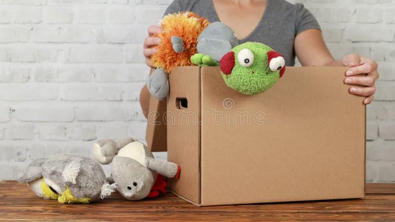Kobieta wolontariusz stawia stare zabawki w darowizny pudełku zdjęcie stock