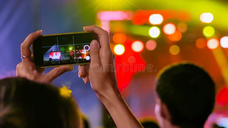 Kobieta wręcza sylwetce magnetofonowego wideo muzyka na żywo koncert z smartphone obrazy royalty free