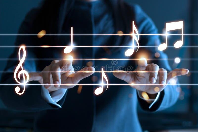 Kobieta wręcza bawić się muzyczne notatki na ciemnym tle, fotografia stock