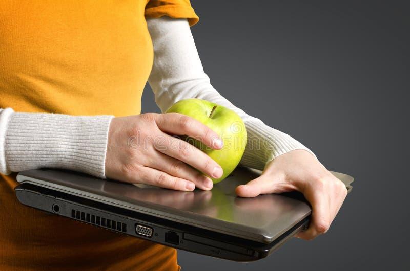 Kobieta wręcza chwytom laptop i żółtego jabłka obraz royalty free