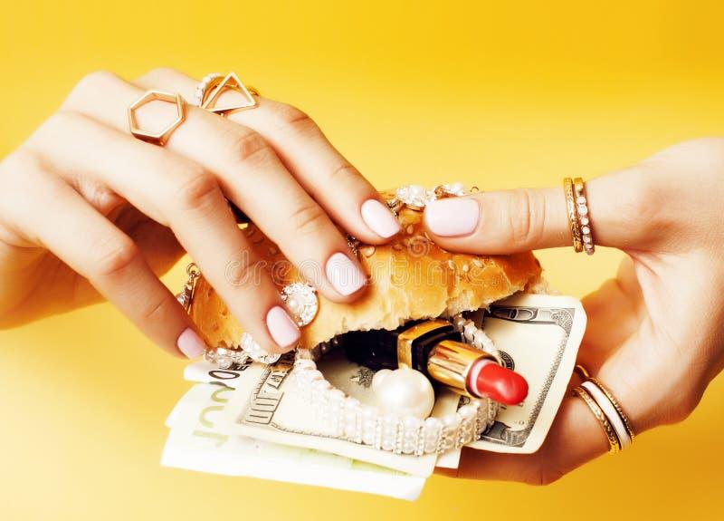 Kobieta wręcza mienie hamburger z pieniądze, biżuteria, kosmetyk, socjalny bogactwa emisyjny pojęcie obrazy stock