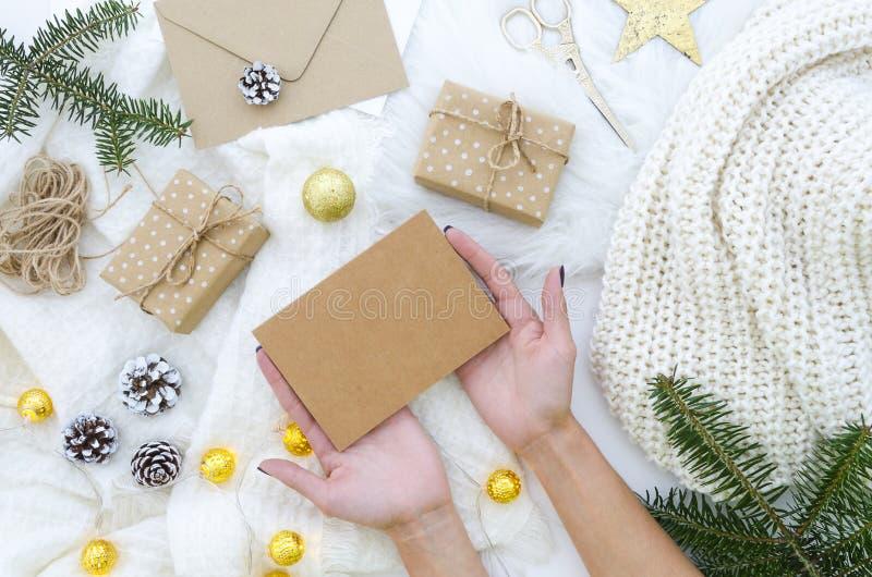 Kobieta wręcza mieniu pustego Kraft papierowy mockup dla Wesoło bożych narodzeń kartka z pozdrowieniami z ręki literowaniem Bożen obraz stock