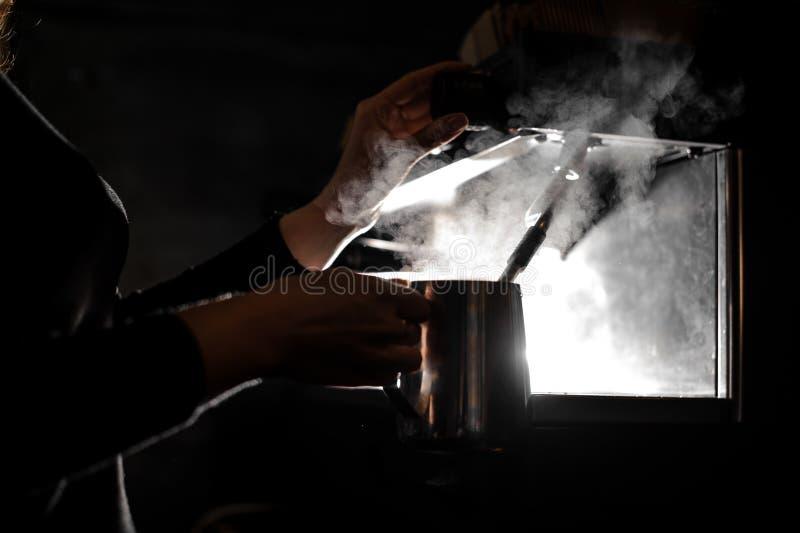 Kobieta wręcza nalewać prawdziwą gorącą wodę w stalowego miotacz fotografia royalty free