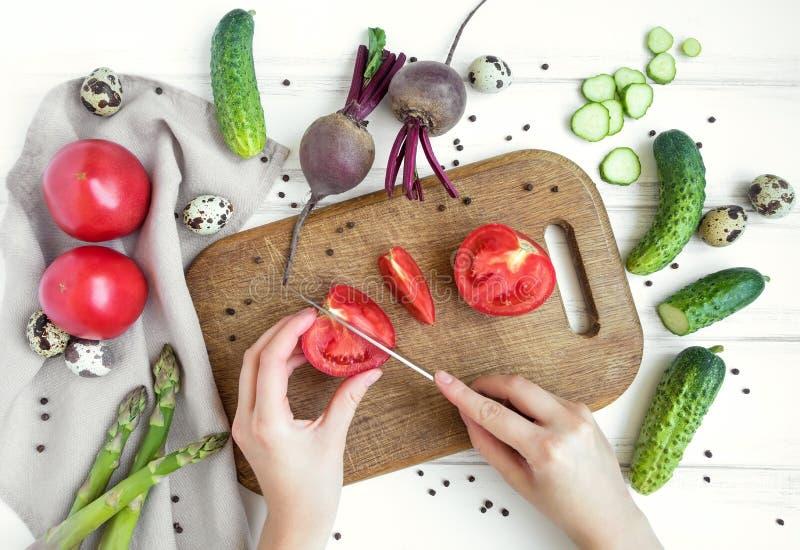 Kobieta wręcza przecinanie pomidoru na drewnianej tnącej desce, otaczającej warzywami Mieszkanie nieatutowy, odgórny widok zdjęcie royalty free