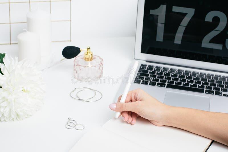 Kobieta wręcza robić notatkom w notepad na białym stole z laptop klawiaturą zdjęcia stock