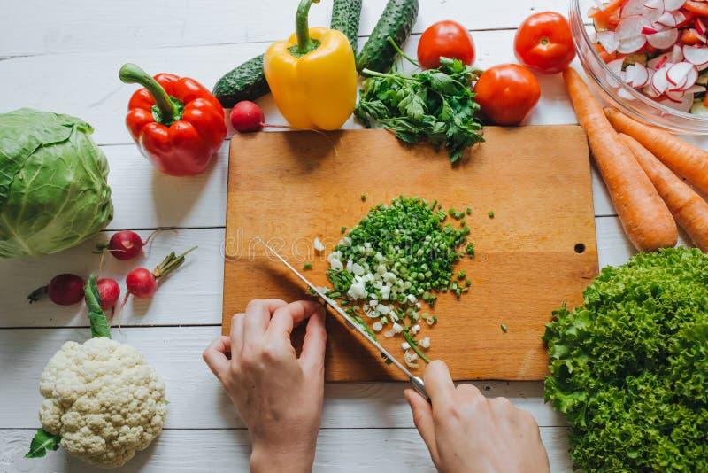 Kobieta wręcza tnącą świeżą zieloną cebulę na drewnianej deski zasięrzutnym odgórnym widoku Bielu stołowy tło Zdrowy kulinarny po zdjęcie stock