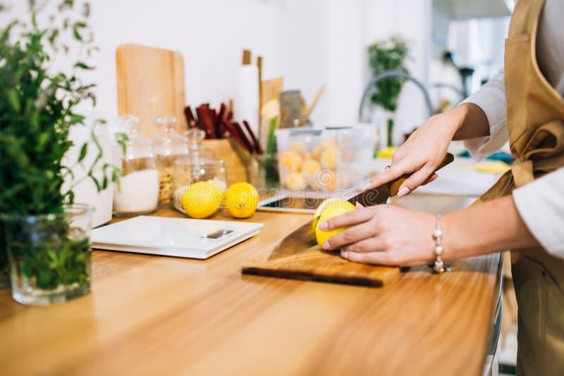 Kobieta wręcza tnącą cytrynę w jaskrawej minimalistic kuchni zdjęcie stock