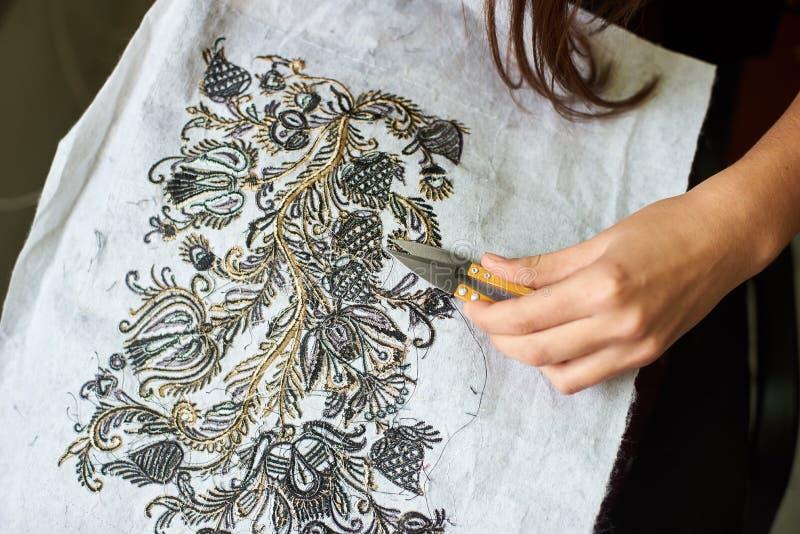 Kobieta wręcza tnące oddalone luźne końcówki nici od tkaniny z maszynową broderią używać nożyce zdjęcie stock