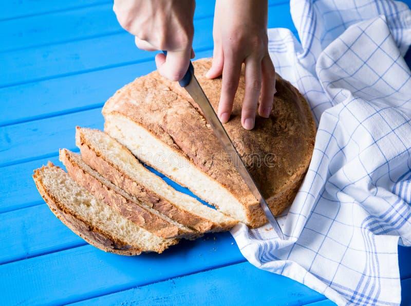 Kobieta wręcza tnącego wheaten chleb na błękitnym drewnianym stole zdjęcie stock
