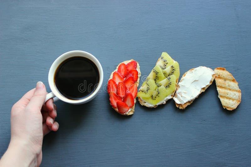 Kobieta Wręcza Trzymać Świeżego filiżanka kawy W Czarnego tła Odgórnym widoku Świeże kanapki z miękkim serem, truskawkami i kiwi, obraz royalty free
