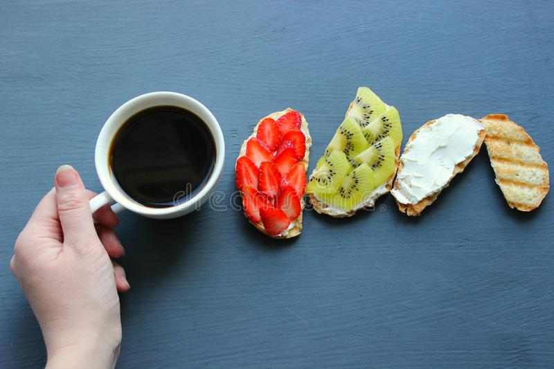 Kobieta Wręcza Trzymać Świeżego filiżanka kawy W Czarnego tła Odgórnym widoku Świeże kanapki z miękkim serem, truskawkami i kiwi, zdjęcie royalty free