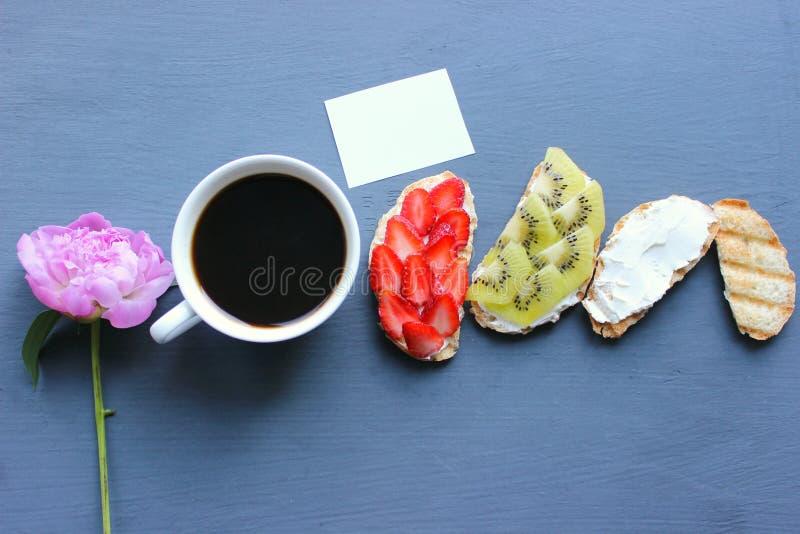 Kobieta Wręcza Trzymać Świeżego filiżanka kawy W Czarnego tła Odgórnym widoku Świeże kanapki z miękkim serem, truskawkami i kiwi, zdjęcia stock