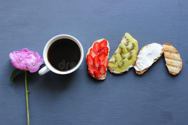 Kobieta Wręcza Trzymać Świeżego filiżanka kawy W Czarnego tła Odgórnym widoku Świeże kanapki z miękkim serem, truskawkami i kiwi, obrazy stock