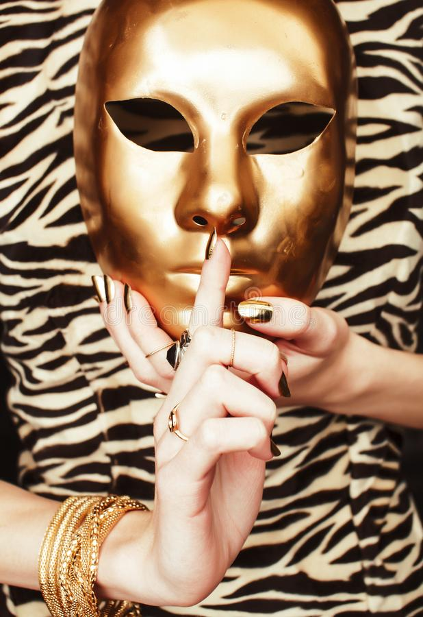 Kobieta wręcza trzymać złotą karnawał maskę, bogatego luksusowego manicure i biżuterię zamkniętą w górę zebra druku na, złocisty  obrazy royalty free