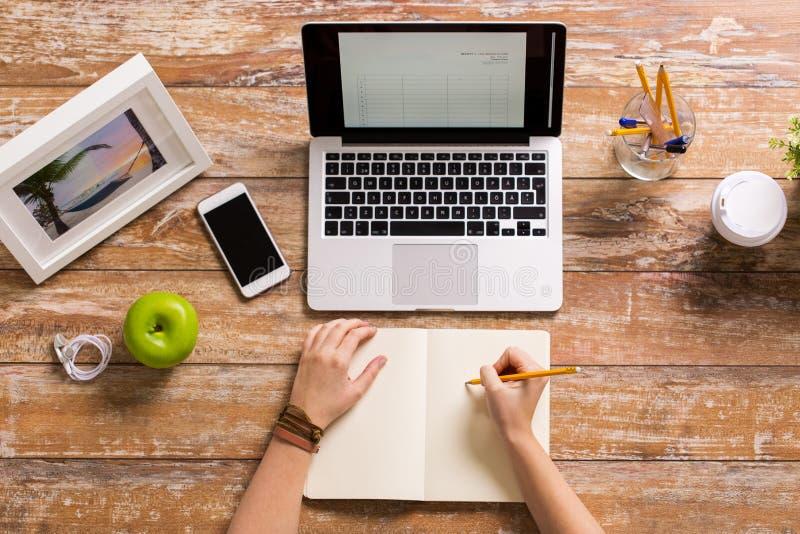 Kobieta wręcza writing notatnika biuro w domu zdjęcia stock