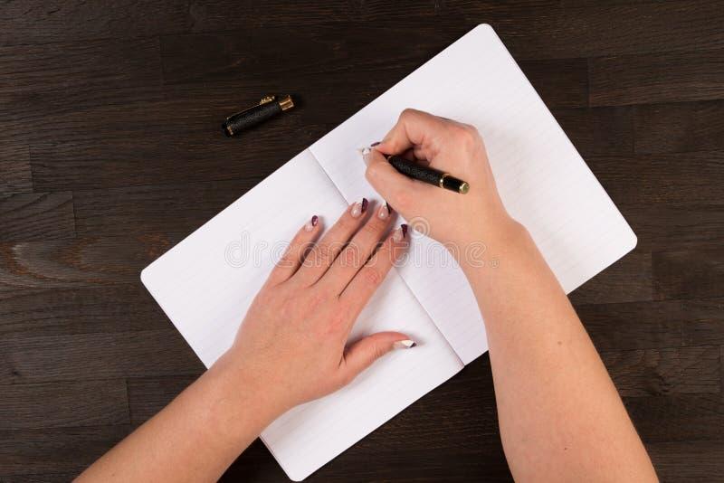 Kobieta wręcza writing w podręczniku obraz royalty free