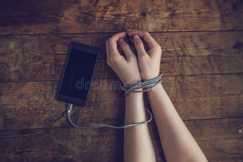 Kobieta wręcza wychwytanego i zawijająca na nadgarstkach z telefonu komórkowego kablem jak kajdankami w mądrze technol telefon ko obraz stock