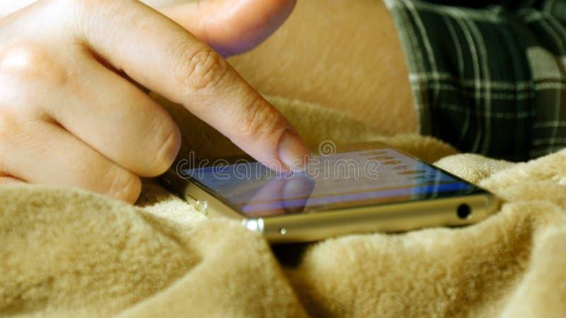 Kobieta wręcza wzruszającego smartphone podczas gdy kłamający na łóżkowym prześcieradle obrazy royalty free