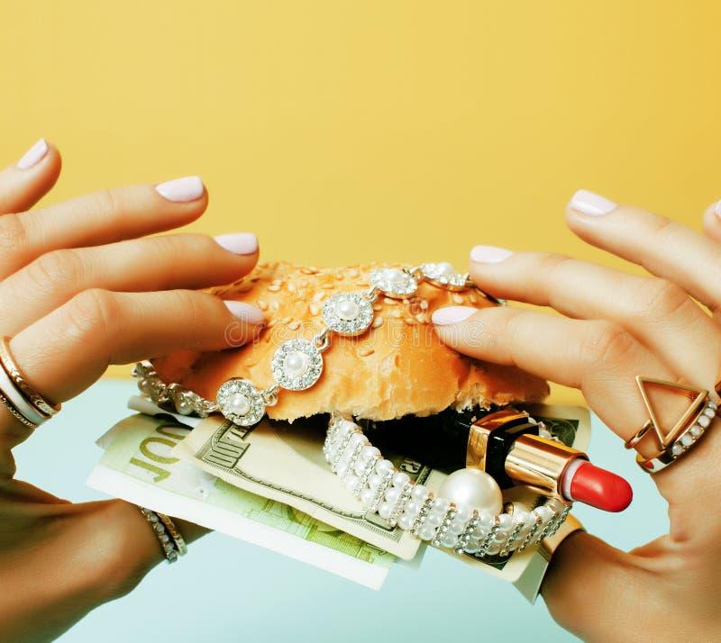 Kobieta wr?cza mienie hamburger z pieni?dze, bi?uteria, kosmetyk, socjalny bogactwa poj?cia emisyjny zako?czenie up zdjęcie royalty free