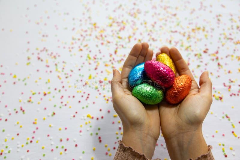 Kobieta wr?cza trzyma? kolorowych czekoladowych Easter jajka z bia?ym t?em i kolorowych zamazanych confetti obraz stock
