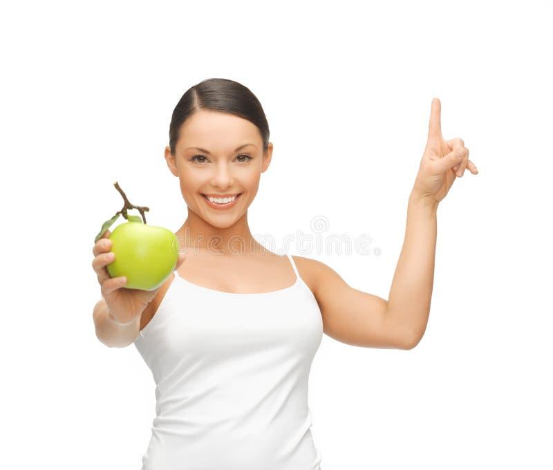 Kobieta wskazuje jej palec up z zielonym jabłkiem fotografia royalty free