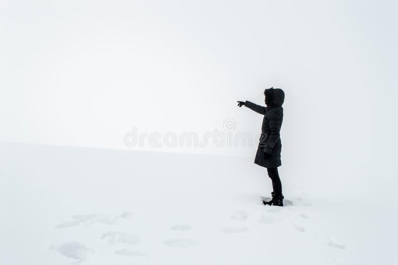 Kobieta wskazuje jej palec w kierunku pustej przestrzeni w śniegu obrazy stock