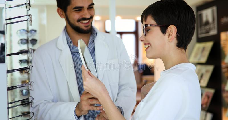 Kobieta wybiera jej nowych szkła przy optyka sklepem z pomocą oftalmolog obrazy stock