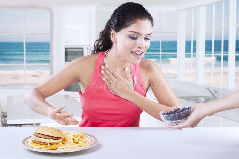 Kobieta wybiera między czarną jagodą lub hamburgerem obraz stock