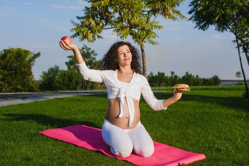 Kobieta wybiera między jabłkiem i hamburgerem obrazy stock