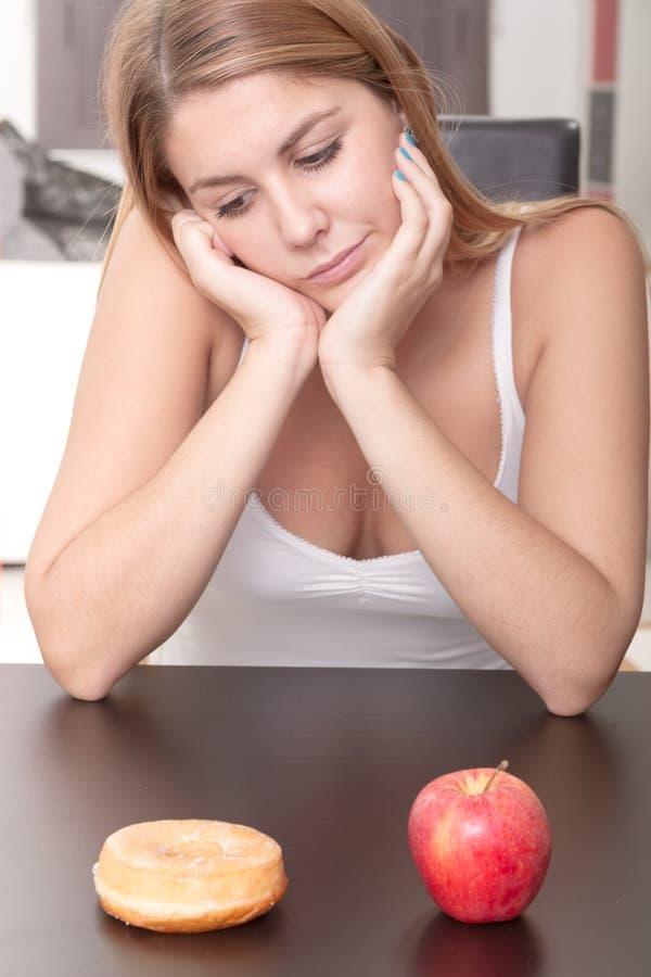 Kobieta wybiera między owoc i cukierkami zdjęcie stock