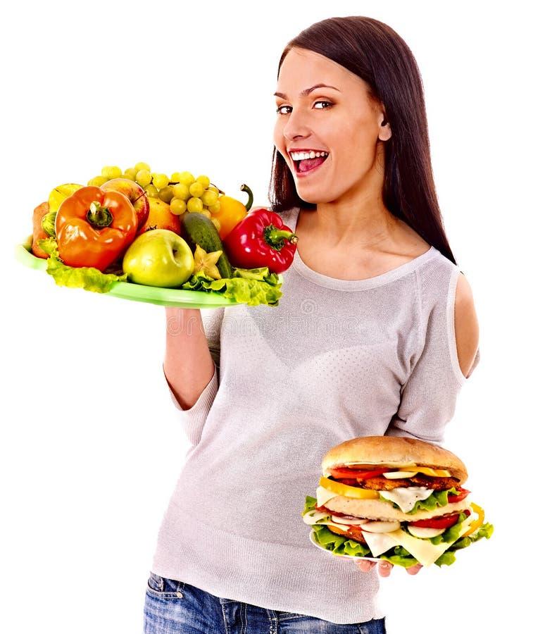 Kobieta wybiera między owoc i hamburgerem. zdjęcie stock