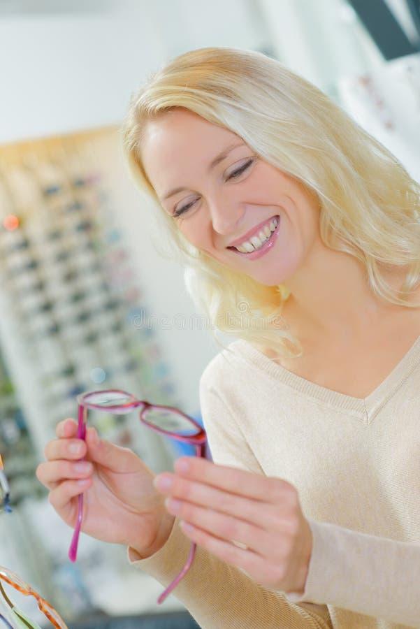 Kobieta wybiera szkła w okulisty sklepie zdjęcie stock