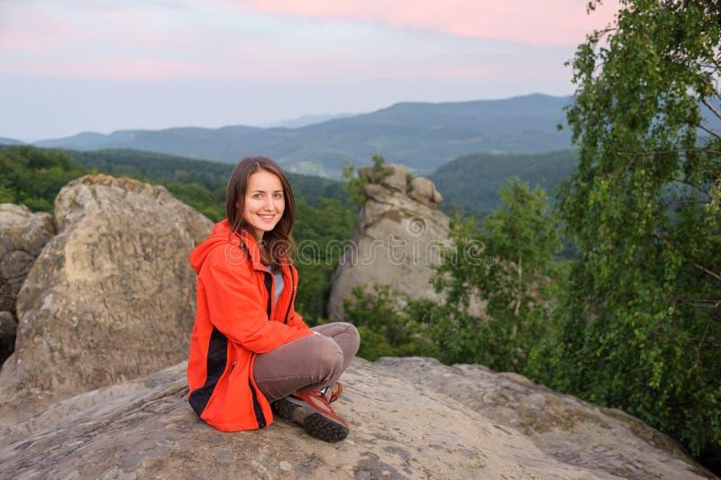 Kobieta wycieczkowicz na dużej skale na górze góry zdjęcie stock