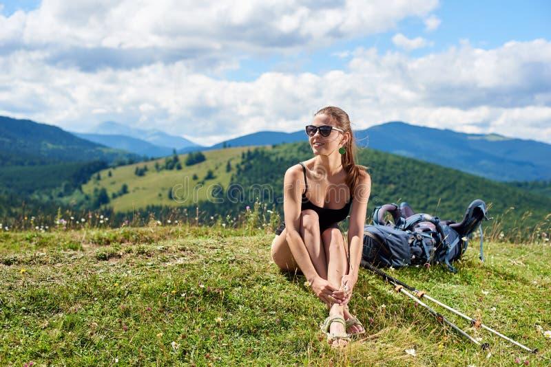 Kobieta wycieczkowicz wycieczkuje na trawiastym wzgórzu, będący ubranym plecaka, używa trekking wtyka w górach fotografia stock