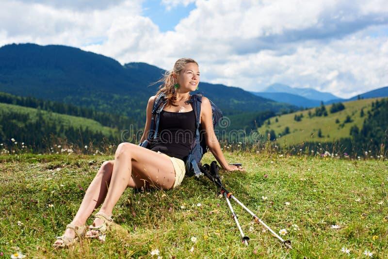 Kobieta wycieczkowicz wycieczkuje na trawiastym wzg?rzu, b?d?cy ubranym plecaka, u?ywa trekking wtyka w g?rach zdjęcie royalty free
