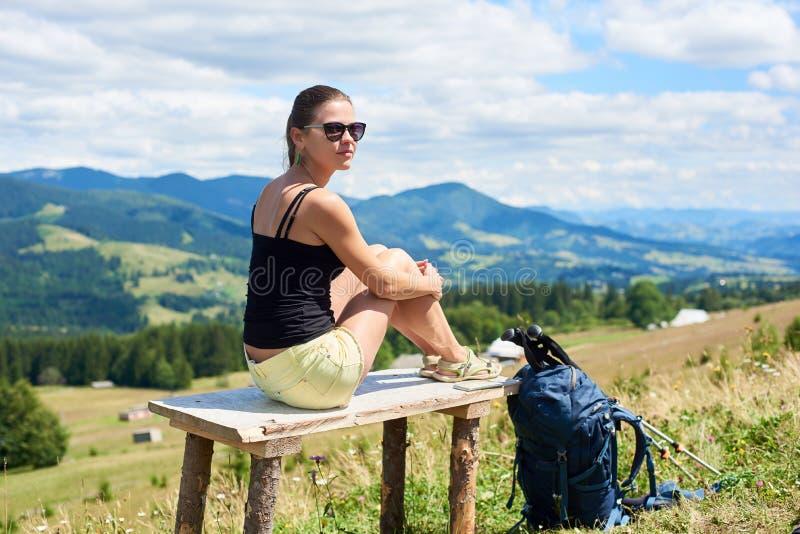 Kobieta wycieczkowicz wycieczkuje na trawiastym wzg?rzu, b?d?cy ubranym plecaka, u?ywa trekking wtyka w g?rach obraz stock
