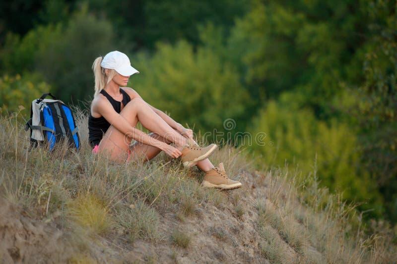 Kobieta wycieczkowicz zdejmował twój buty lub rozluźnia twój shoelace fotografia royalty free