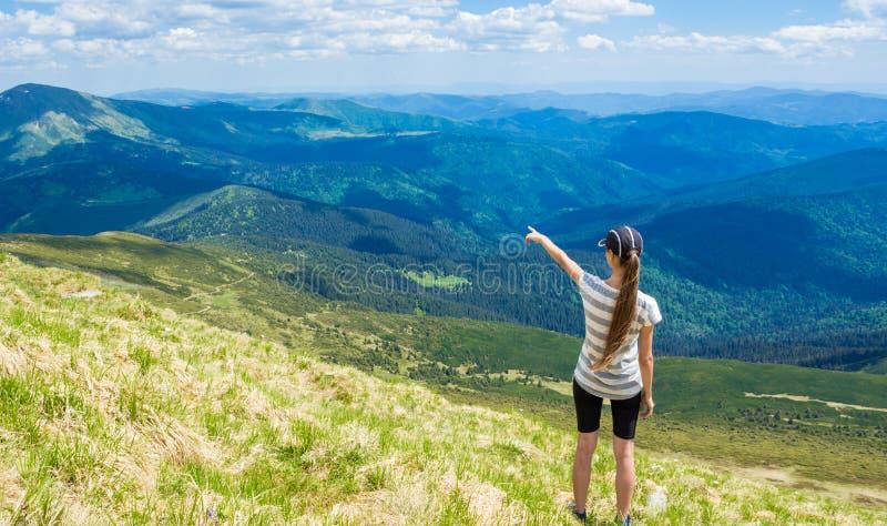 Kobieta wycieczkuje wskazywać niebo cieszy się pięknego widok przy górą obrazy royalty free