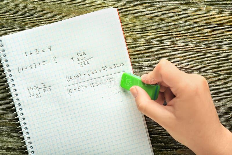 Kobieta wymazuje błąd w notatniku z matematyki równaniem, odgórny widok zdjęcie stock