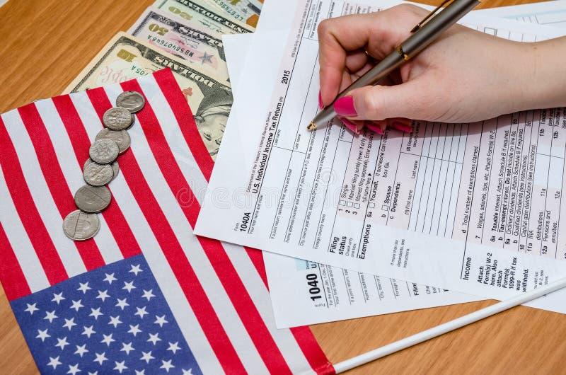 Kobieta wypełnia podatek formę 1040 z pieniądze, piórem, flaga usa i kalkulatorem, zdjęcie stock
