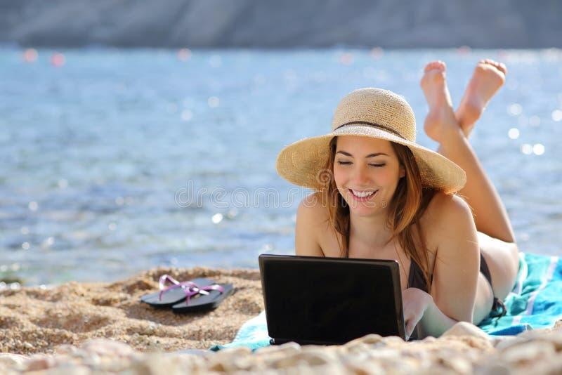 Kobieta wyszukuje ogólnospołecznych środki na komputerze w lecie na plaży obraz royalty free