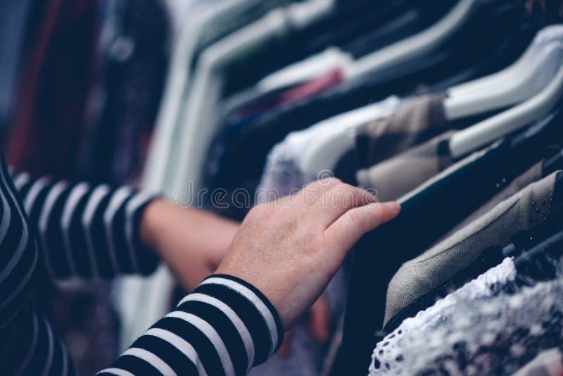 Kobieta wyszukuje przez odzieży przy drugi ręki ulicznym rynkiem zdjęcie stock