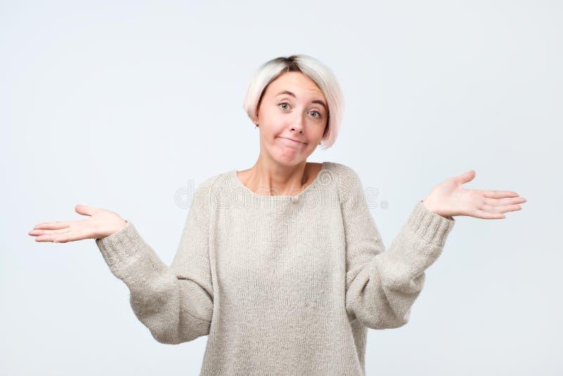 Kobieta wzrusza ramionami ramiona jak no zna odpowiedzi, być nieświadomy i niepewny obraz royalty free