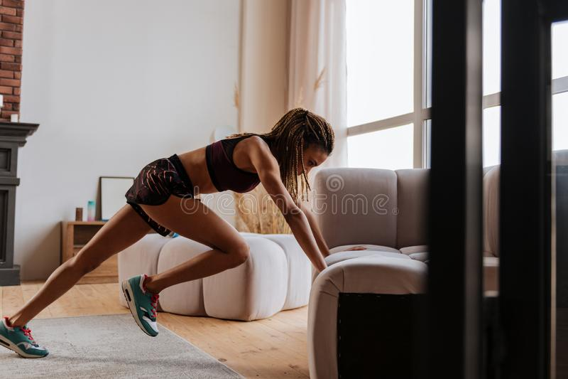 Kobieta z ładnym sporta ciałem robi intensywnym ćwiczeniom w domu obraz stock